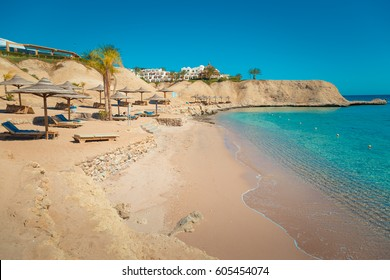 Beach on the shore of the Red Sea. Sun beds and umbrellas. Resort in the desert. Egypt