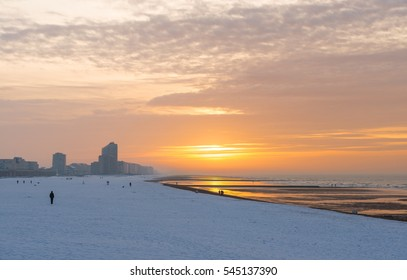 The beach of Oostende covered in snow during winter with a part of its skyline, Belgium.