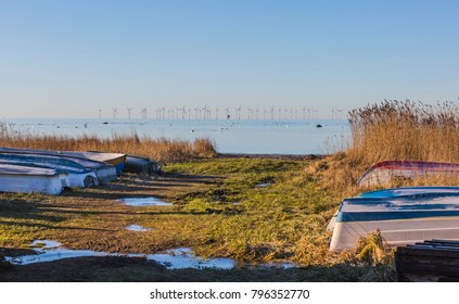 The beach of Oresund with landed skiffs and an offshore wind power station in the background  a cold winter day