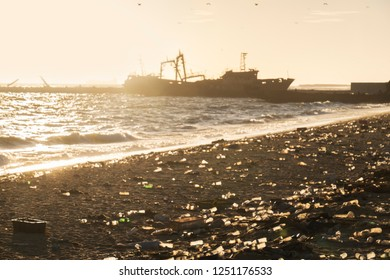 Beach overloaded with ship wreck plastic garbage in sunrise