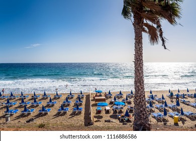 beach with palm and ocean in Puerto del Carmen, Spain. Puerto del Carmen is the main tourist town on the island of Lanzarote