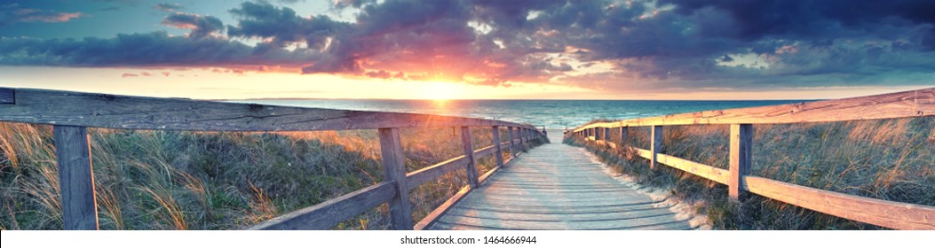 beach panorama - wooden path to the sea at sunset