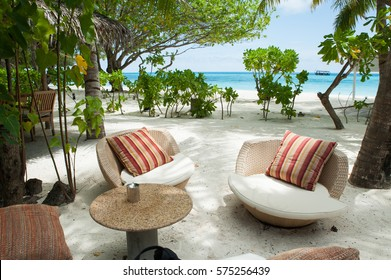 Beach paradise island in Maldives. Two chairs with cushions with luxurious drapes and table for guests in the foreground. In the distance the turquoise sea and green palm trees , white sand. .