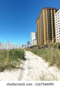 Beach path along the dunes with oceanfront development.