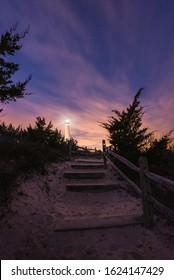 Beach path leading towards Barnegat Lighthouse under the starry night sky