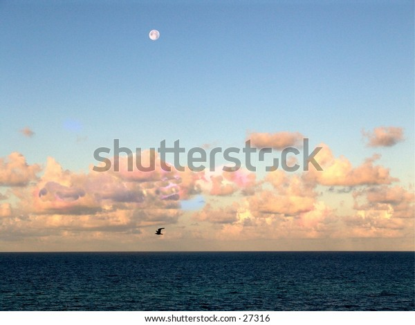 beach photo in june with the sun riseing behind the clouds and the moon still showing.