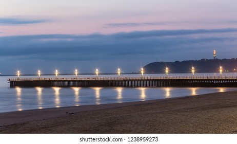 Beach pier jetty lights long photo exposure reflections at dawn morning  Durban harbor port entry beachfront.