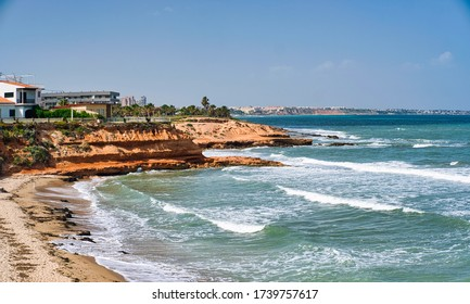 Beach of Pilar de la Horadada, rocky coastline idyllic landscape, turquoise wavy waters of Mediterranean Sea during sunny warm day. Costa Blanca, Province of Alicante, Europe, Spain