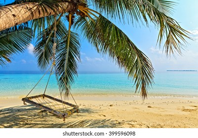 Beach place for relax under the shade of a palm tree