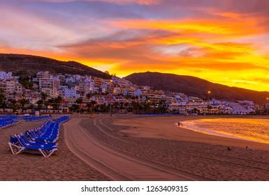 Beach Playa de Las Vistas with sun loungers at sunrise on Tenerife, Canary Islands, Spain