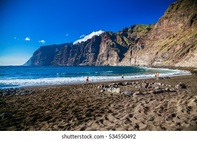 beach Playa de los Guios in Los Gigantes with four running men, Tenerife, Canary Islands, Spain