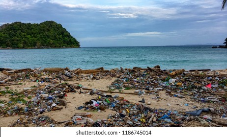 Beach pollution, plastic and waste from ocean on the beach. Pollution on the beach of tropical sea. Waste on beach with blue sea background.