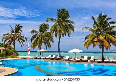 Beach pool in a tropical hotel Palm Beach. Maldives, The Indian Ocean