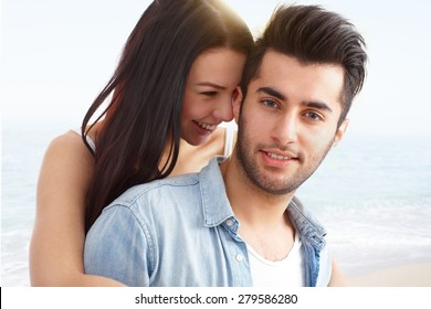 Beach portrait of young attractive loving couple, embracing and smiling happy.