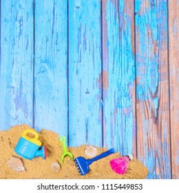 Beach poster on wooden background with sand and plastic toys