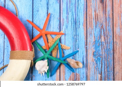 Beach poster on wooden background with starfishes and life buoy