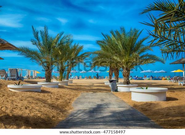 Der Strand von Ras Al Khaimah mit Sonnenschirmen und Liegen.