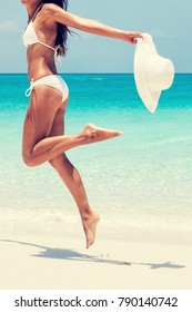 Beach ready bikini body - sexy lean legs and thighs cellulite laser treatment or hair removal. Suntan happy woman jumping on white sand with sun hat. Weight loss success or epilation concept.