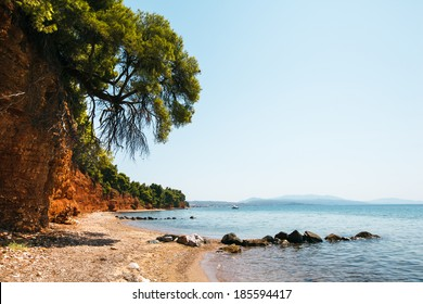 Beach with red land and green pines in Metamorfosi, Greece