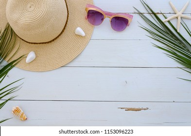 Beach relaxation board presentation with summer hat, sun glasses, palm leaves and sea shels on white planks background. Perfect for lettering.