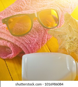 Beach resort concept. Female beach accessories on a blue yellow wooden background. Shell, glasses, towel, sunblock.