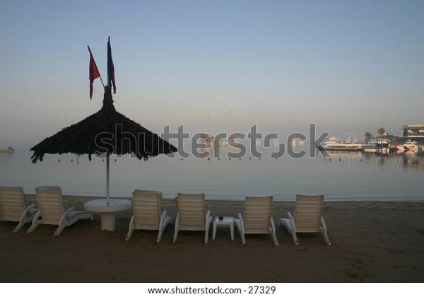 Beach resort and marina on a misty morning at dawn in Qatar, Arabia. An Arab dhow is among the boats in the background.