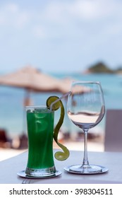 Beach restaurant with sea view, glasses, plates, food, tropical colorful cocktail with ice
