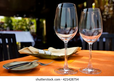 Beach restaurant with sea view, table with empty wine glasses, plates