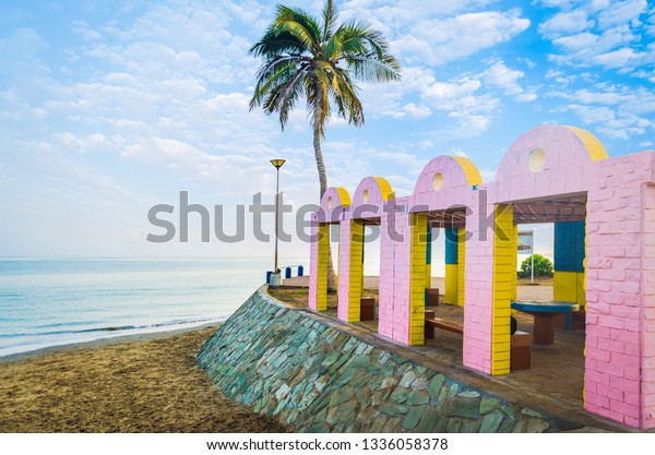 Beach Resting Place with pink and yellow bricks with calm sea and a lone coconut tree in the background. From Muscat, Oman.