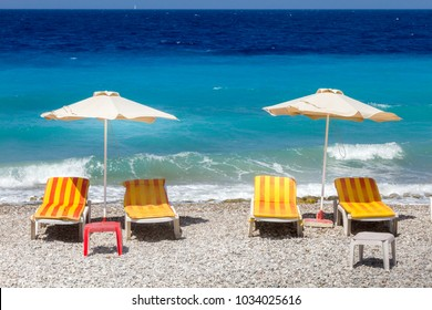 Beach in Rhodes, Greece, with sunbeds and sea umbrellas.