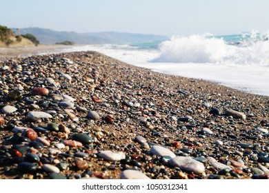 Beach at Rhodes with stones and beautiful sea on the mountais background