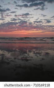 Beach Right Before Sunrise With Pink Clouds Reflecting on the Wet Sand