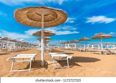 Beach in Rimini. Italy. Sun umbrellas on blue sky background on seashore. Summer background.