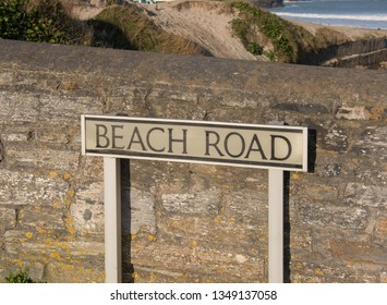 """Beach Road"" Sign Post by a Stone Wall in the Seaside Fishing Village of Portreath on the South West Coast Path in Rural Cornwall, England, UK"