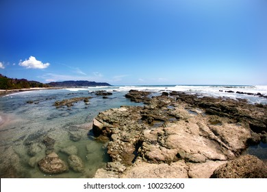 Beach with rock formations in the ocean with waves approaching and blue sky near sand and forest