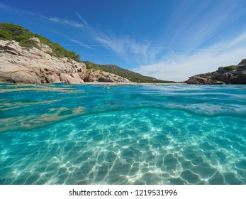Beach and rock on seashore with sand underwater, split view half above and below water surface, Mediterranean sea, Spain, Costa Dorada, Platja Del Torn, l'Hospitalet de l'Infant, Tarragona, Catalonia