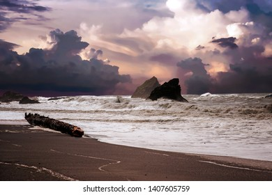 beach and rocks and wild waves on a cloudy rainy day