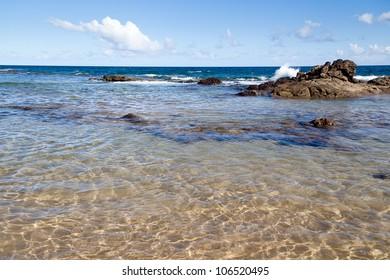 Beach of Salvador, Bahia Brazil. Shows waves splashing on the rocks and transparent sea water. Blue sea and sky.
