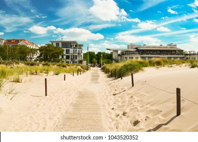Beach sand, blue sky with clouds, hotels, tall grass. The beach of the Baltic Sea, Germany.