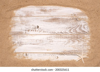 Beach sand on wooden background with small star fish and plenty of copy space