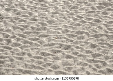 Beach sand with pattern of ridges, like a washboard, along intertidal zone on barrier island, for background or element with themes of cause and effect