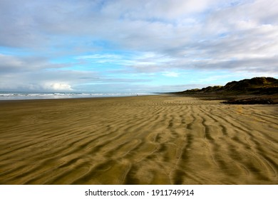 Beach sand striations with small waves and cloudy sky