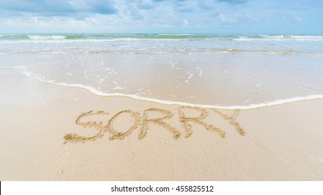 """beach sand with text write on it """"SORRY"""""""