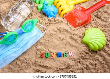 Beach sand with toys for the baby, water, the word summer in colored letters. Staycation content