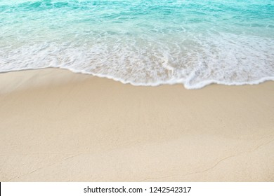 Beach sand and white foamy blue wave on day light,Shore background well use editing for present or text on your projects.