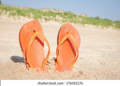 BEACH SANDALS IN SAND Orange flip flops in beach sand in front of dunes.