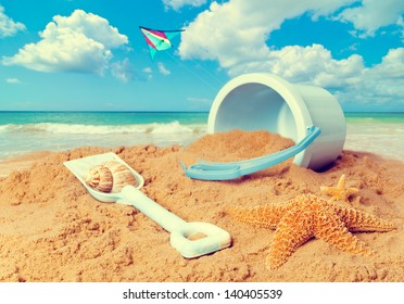 Beach scene with bucket and spade against ocean background with kite flying