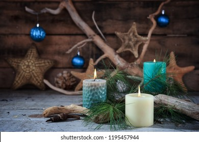 Beach scene of Christmas candles and seaside decor with blue ornaments on a wooden background