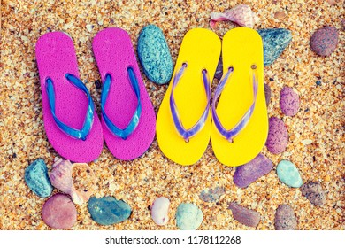 Beach scene. Flip flop sandals lying on sea coquina
