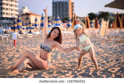 Beach scene. Happy woman and child on beach sand in Rimini. Summer vacation scene.